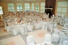 Wedding Decor- White Linen, White Chair Covers with Silver Bows and 3 Cylinder Floating Candle Centerpiece surrounded by Red Glass Gems