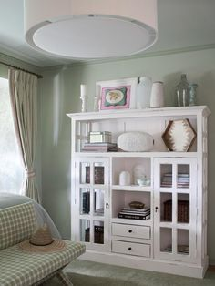 Favorite keepsakes are displayed inside and on top of an antique wooden bookcase. For a balanced look, books are displayed both vertically and horizontally, then combined with various objects ranging in size, color, shape and texture.