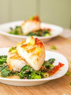 This seared Chilean Sea Bass recipe features a fillet topped with wilted sesame spinach and drizzled with a spicy, sour sweet Vietnamese inspired sauce.