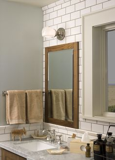 Sure it's a bathroom, but the color combo is wonderful. Warm brown wood (mirror), grey (walls), white (tile) and a schoolhouse-ish style light.  Love the tan towels paired with grey walls and counters.  Need to transfer this color scheme to the kitchen.