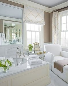 How wonderful to have a chaise by the tub to make this a truly relaxing bath! The roman shades add a touch of color and privacy without taking away from the natural light.