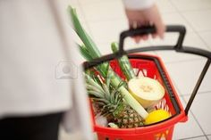 hands shopping vegetables: High angle view of human hand carrying red basket filled with fruits and vegetables