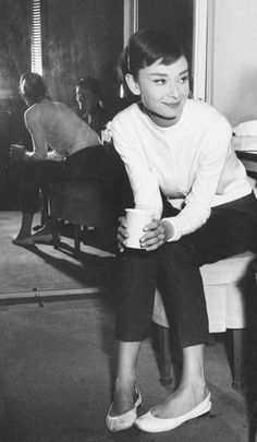 Audrey Hepburn, style muse (and idol in many ways,) in white cardigan. slim, dark cropped pants. White ballet flats