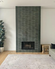 Handmade fireplace tiles in an artisanal green anchors this condo living room with its one-of-a-kind color variation. Tiled Fireplace Wall, Fireplace Tile Surround, Home Fireplace, Fireplace Remodel, Brick Fireplace, Fireplace Surrounds, Fireplaces, Tile Around Fireplace, Fireplace Makeovers