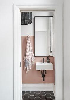 This contemporary pink and black powder room boasts large black hexagon floor tiles contrasting a wall mounted sink fixed beneath a mirror hung from a white and pink painted wall. Pink Bathroom Decor, White Bathroom Tiles, Bathroom Interior, Black And White Bathroom Floor, Upstairs Bathrooms, Downstairs Bathroom, Small Bathroom, Small Downstairs Toilet, Pink Toilet