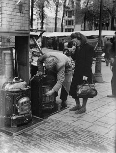 1940. Couple inspects coal stoves offered for sale at the Waterlooplein in Amsterdam. #amsterdam #1940 #waterlooplein
