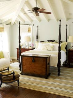 Bedroom  An airy paneled ceiling in the master bedroom takes advantage of the roof pitch. A four-poster bed based on an Indonesian antique contrasts with the whispery blue walls. French doors open to the front master-bedroom veranda.