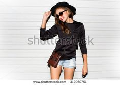 Young girl doing emotion.Dressed in a black shirt, black sweater,black hat,glasses and bright lips,trendy clothes.wearing vintage sunglasses,outfit and hat,vacation style,bright colors.Sensual woman - stock photo