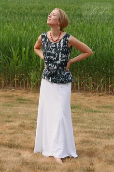 Modest and Feminine outfit idea: long white skirt, scalloped sleeveless black and white top, and red necklace.