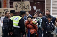 """CHINA-EARTHQUAKE/An earthquake survivor carries a baby and a sign that reads, """"Serious disaster need help"""" as she and other villagers protest against what they said was a lack of rescue operations at Chaoyang village, after Saturday's earthquake in Lushan county of Ya'an, Sichuan province April 22, 2013. Rescuers struggled to reach a remote, rural corner of southwestern China on Sunday as the toll of the dead and missing from the country's worst earthquake in three years climbed to 208 with…"""