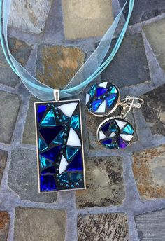This glass mosaic pendant with silver bezel features hand-cut white stained glass and blue and turquoise ripple mirror glass. A blue ball chain runs through the center of the bezel tray. Black grout was used to bring out the colors. Grout sealant was used to protect this work of