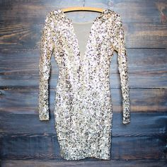 An amazing gold sequin dress that features long sleeves, a mesh front v panel, a deep v back neckline, and a hidden zipper with hook closure. This perfect number will go so well for multiple occasions