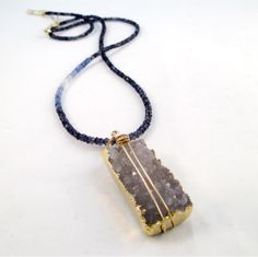 A removable drusy agate pendant coupled with a long strand of iolite gemstones accented with light blue and white sapphires and 14k rolled gold