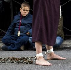 A young boy watches as a penitent walks with chains around his bare feet during a silent Semana Santa (Holy Week) procession in Madrid, Friday April 6, 2012, Hundreds of processions take place throughout Spain during the Easter Holy Week. (AP Photo/Paul White)