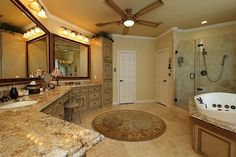 Luxurious master bathroom with granite counters, travertine floors and upgraded hardware