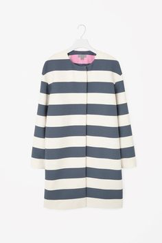 This round-neck coat is made from lightly textured fabric with an all-over striped pattern and contrast block-colour detail along the back. Slightly oversized, it has long sleeves, in-seam side pockets and a hidden zip fastening for a clean, minimal front.