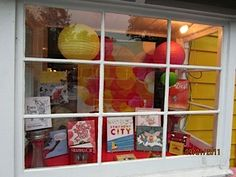 The Golden Notebook window display via McSweeney's. Colorful paper lanterns and background.
