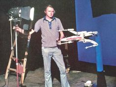 "ILM artist Dennis Muren prepares to photograph an X-Wing fighter for ""STAR WARS."""