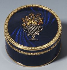 Fabergé circular box in engraved red gold and enamelled translucent royal blue guilloché enamel, with green gold chased foliate borders, the cover applied with a rose diamond basket of flowers set with three cabochon rubies and two emeralds. Workmaster Henrik Wigström, 1908.