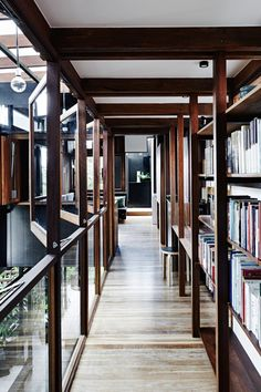 Modern wood and glass walkway lined with bookshelves