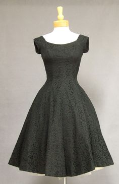 A true classic in black lace from the 1950's. Scooped neck and back and cap sleeves. Dress has a figure flattering vertically seamed fit and flare shape. This is perfection of line and shape.