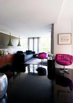 glossy black floors, pendants, black sofa and fun fuchsia chairs