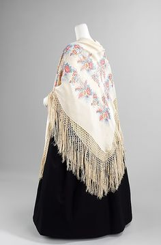 Fringed silk shawl, probably French, 1840-49. This shawl interestingly combines a woven pattern and printed pattern, incorporating both Eastern and Western aesthetic sensibilities. The shawl held a place as a high fashion accessory for a relatively large period between the end of the 18th century to the 1870s. These objects were hand woven and extremely costly which inspired European manufacturers to attempt to produce cheaper copies for the masses.