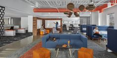 Another breakout space and work lounge features more Niche modern orb pendants. Our signature Gray glass helps to balance out the bold blues and oranges featured prominently throughout the interior, which beautifully reflect HubSpot's branding. Photo 4 of HubSpot Offices modern home