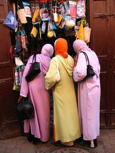 Moroccan women shopping in Marrakech, wearing typical djellabas (the draping hood is signature Moroccan) and matching hijab (head scarves).