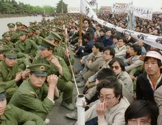200,000 pro-democracy student protesters sit face to face with policemen outside the Great Hall of the People in Tiananmen Square on April 22, 1989 in Beijing during an unauthorized demonstration to mourn the death of Chinese Communist Party leader and liberal reformer Hu Yaobang.