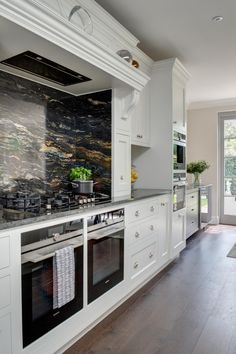 Bespoke hand made kitchen, white hand painted kitchen, Siemens appliances, overmantle, false chimney, granite worktops, cosmic black granite,