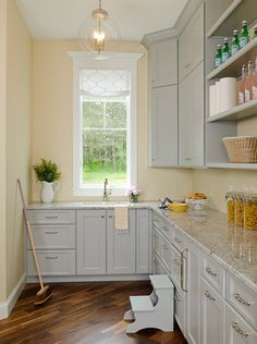 Family Home Interior IdeasThis butler's pantry features a delicate wallpaper on walls that calmly contrast with pale gray cabinets and gray granite countertop.