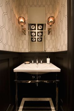 Chic powder room with trellis wallpaper paired with high gloss black wainscoting.