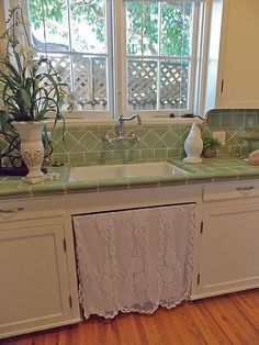 curve faucet in wall above sink, the tile for counters and back splash. ADD an Apron front sink and this would be my dream set up!