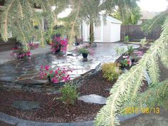 A low two-tiered flagstone patio wraps around the back of this house to the side yard. A transition zone of lava rock, stepping stones, and shrubs are contained by stamped concrete curbing. Picture compliments of Dream-yard.