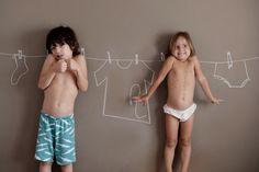 Ensaio de fotos de crianças sorrindo e brincando com giz na parede