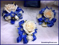 Pearl bracelet wrist corsages of white roses and blue delphinium.