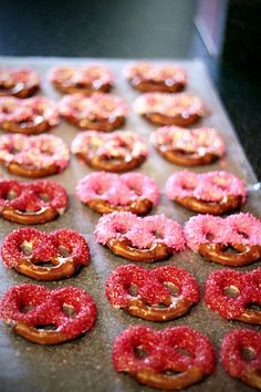 Valentine Pretzel Treat. Melt white chocolate or almond bark and dip pretzels & top with colored sprinkles.