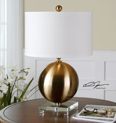 Uttermost Laton Brass Sphere Table Lamp. Brushed brass plated metal accented with a thick crystal foot. The round hardback drum shade is an off white linen fabric.