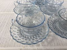 ~ Vintage Blue bubble Glassware, Anchor Hocking Blue Bubble Cup and Saucer- Blue Depression Glass, 1940s Glassware, Blue Tea cup and saucer ~  **Listing cost is for 4 cups and saucers **  MAKER: Anchor Hocking PATTERN: Blue bubble CIRCA : 1942 - 48 Discontinued Measurements: Cup - 2 1/4 tall and Holds 8 ounces Saucer - 5 3/4 diameter VERY GOOD vintage condition - No chips, cracks, discoloration or rough edges on the rims. Glass is bright and clear and free from clouding. As with any...