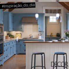 A delicadeza do azul confere elegância à cozinha. Em madeira, a composição do mobiliário remete à essência rústica, já os sofisticados pendentes e as banquetas em metal conferem um toque contemporâneo ao décor. Também presente no ambiente, o branco sugere uma atmosfera leve e clean.
