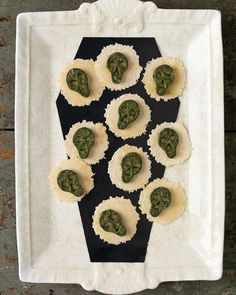 """You'd never guess these tiny skulls are actually quite wholesome for a Halloween party. They're cut from a baked custard of spinach, basil, and ricotta cheese, then arranged on crackers. A black cardstock """"coffin"""" makes a fitting bed for the skeletal snacks."""