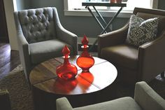 Orange decanters on coffee table. Homearama 2016 - Lounge - Robin's Nest Interiors. Designed by Robin Cole of Robin's Nest Interiors.