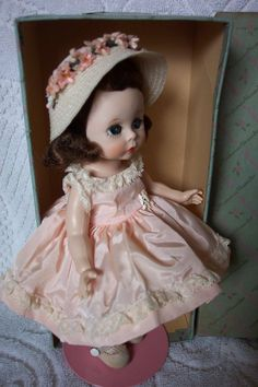 """This doll has the face of an ANGEL. with rosy cheeks, """"pouty"""" lips and lots of finely feathered painted lashes. I'm sorry but I don't know the name of her costume. Her white shaped woven hat with loads of tiny velvety rich pink flowers is to die for.! 