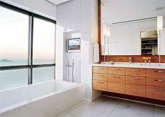 Este banheiro ocupa hoje parte da sala e ganhou as grandes janelas, que proporcionam um visual perfeito para curtir o banho na hidromassagem. Quase todo o espaço é revestido de mármore calacata ouro, exceto a parede atrás do espelho, de peroba lustrada, assim como o armário da bancada. Projeto de Cynthia Pedrosa. Alcove, Architecture Design, Bathtub, Bathroom, Bb, Room Mom, Wooden Cupboard, Large Windows, Restroom Decoration