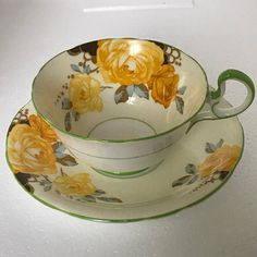 Aynsley Tea Cup and Saucer in unusual yellow green and black rose design.  Perfect Vintage Condition  1950s Made in England