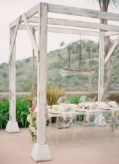 rustic shipwreck wedding with ghost chairs and amazing ship chandelier.