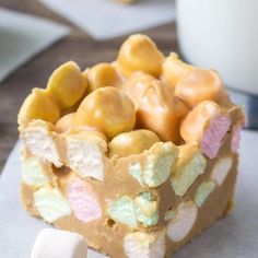 Confetti square made with rainbow marshmallows, butterscotch chips & peanut butter with a glass of milk and 2 squares in the background