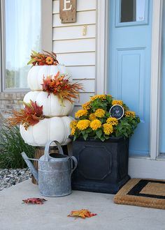 We love these cheery fall front door decorations by April Hoff of House by Hoff. She mixes pumpkins and fall mums with a few rustic items for a lovely fall front porch. Check out her fall decorating ideas on The Home Depot Blog. || @aprilhoff