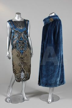 An orientalist embroidered and sequined tabard, circa 1925, the black organza ground worked with palmettes in electric blue, silver and black sequins, large facetted beads, with a textured gold metallic silk skirt, open sides, together with a soft blue velvet evening cape with padded collar, scarf panel with gold fringed tassel